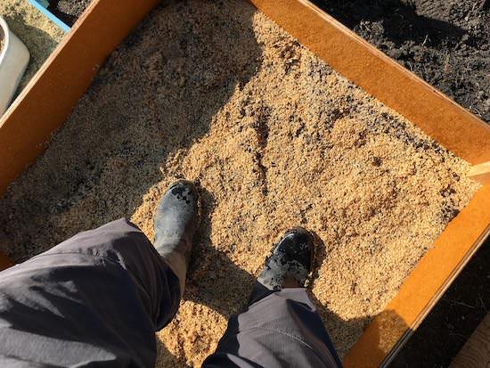 もみ殻堆肥の材料を足で踏み固める