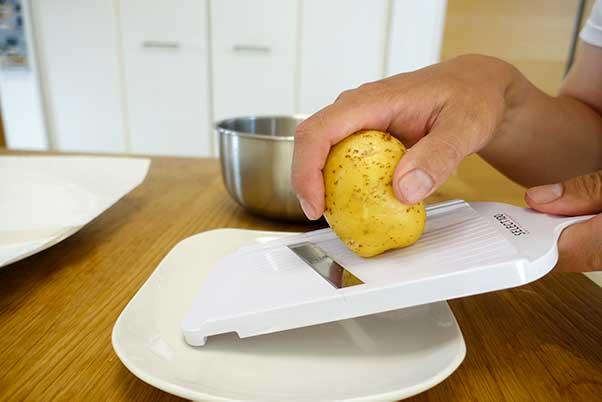 ジャガイモをスライサーで薄切りにする